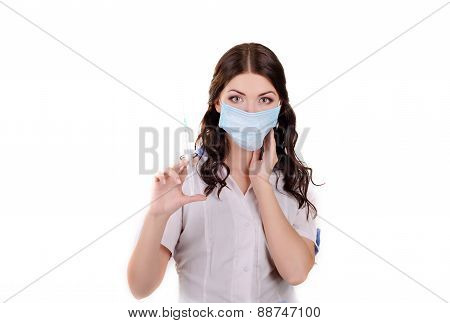The girl the doctor in a medical mask with a syringe