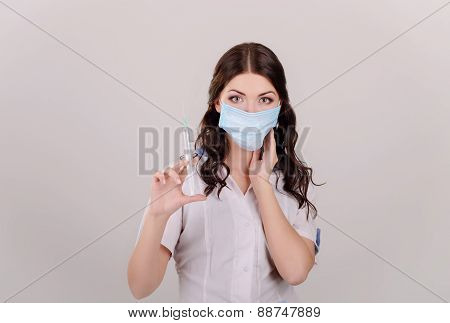 the doctor in a medical mask with a syringe