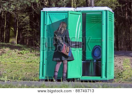 Girl At A Portable Toilets At An Outdoor