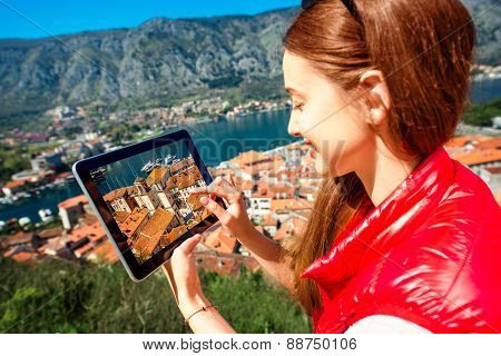 Woman photographing with tablet old city