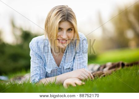 portrait of a beautiful woman laying in the grass with a smile