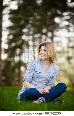 portrait of a beautiful woman sitting in grass