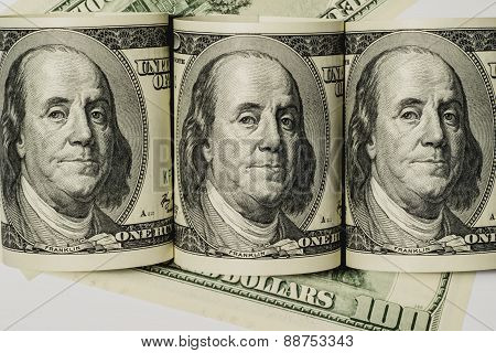 Rolled up one hundred dollar bills