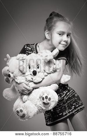 one girl holds the armful of toys