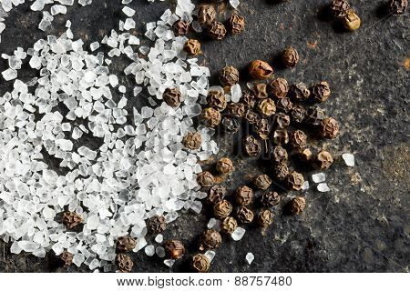 top view of  salt crystals and black peppercorns