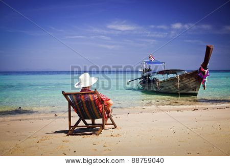 Exotic beach holiday background with woman sitting in beach chair and long tail boat - Thailand ocean landscape