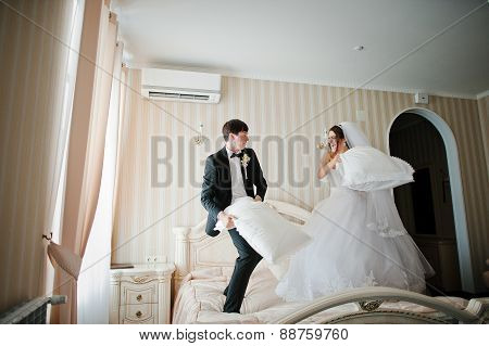 Young Beautiful Wedding Couple At The Hotel Room Fight Pillow