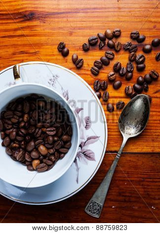 Coffee Beans And Cup On Wooden Table