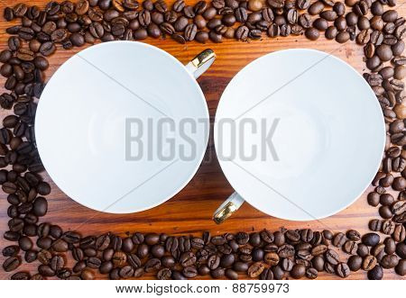 Coffee Beans And Two Empty Cups On Wooden Table