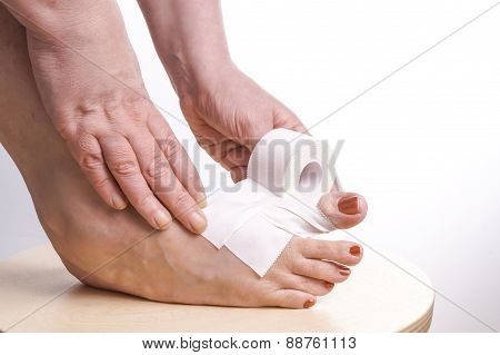 Hands Rolling Therapeutic Self Adhesive Tape On A Foot