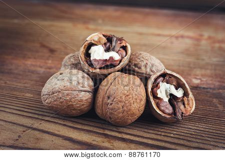 Walnut kernels and whole walnuts wood background