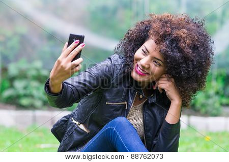 exotic beautiful young girl taking a selfie sitting in the garden