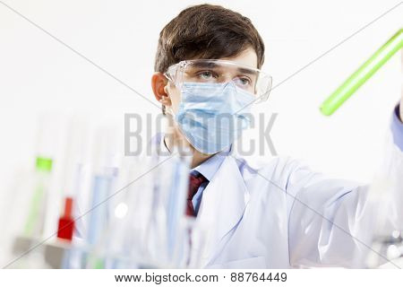 Young scientist making chemical tests in laboratory