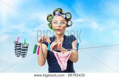 Woman hanging wet clothing with clothespin on clothes-line. Outdoor, outside.