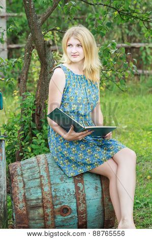 Blonde Student Girl In Feminine Blue Silk Dress With Opened Book