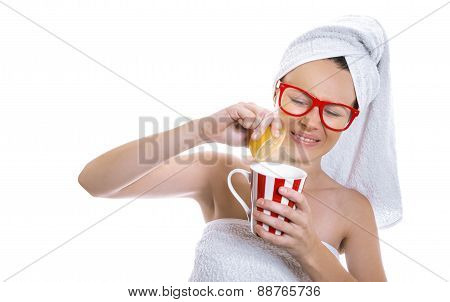 Young Expressive Girl Holding Hot Tea Mug And Squeeze Lemon Over White Background. Bitter Or Sour Dr