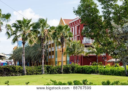 Colorful Plaster Resort Through Palm Trees