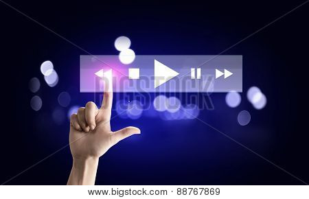 Close up of hand pushing icon of media player