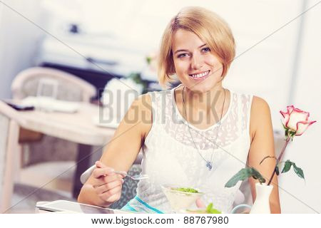 Image of young and pretty woman having dessert in cafe