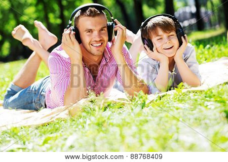 Father and kid in summer park enjoying music