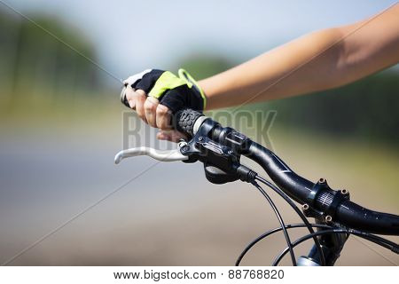 Close up of young woman riding a bicycle in a park