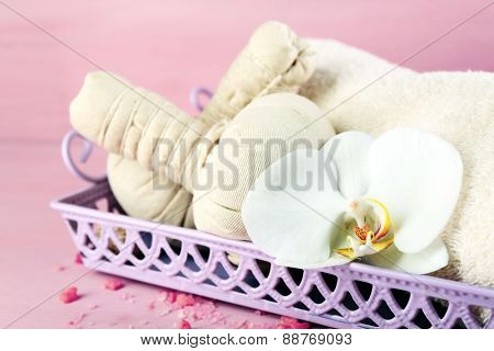 Still life with beautiful blooming orchid flower, spa treatment on tray, on color wooden background