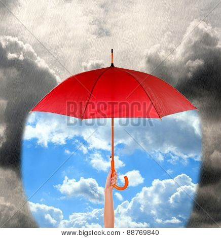 Red umbrella in hand protecting good weather from dark clouds of rain