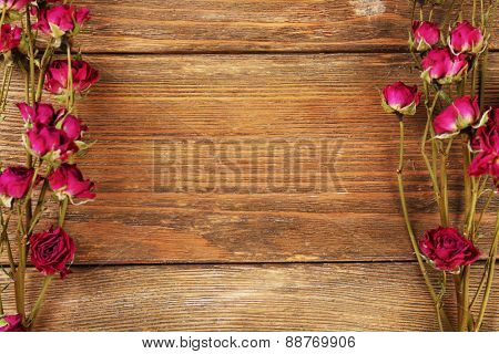 Frame of dried flowers on wooden background