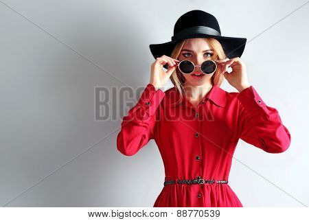 Expressive young model in red dress, black hat and sunglasses on gray background