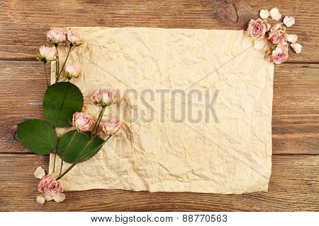 Dried roses on sheet of paper on wooden table, top view