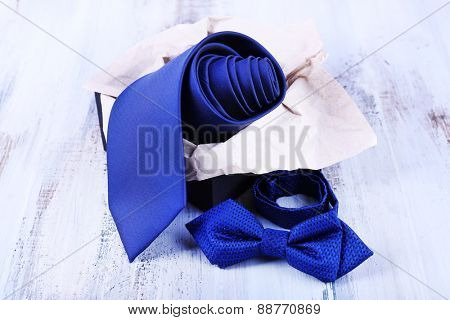 Male necktie and bow tie in box on wooden background