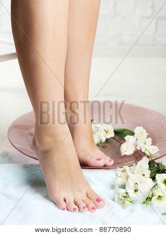 Beautiful female legs on  towel, on light  floor background