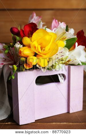 Beautiful spring flowers in wooden crate, closeup