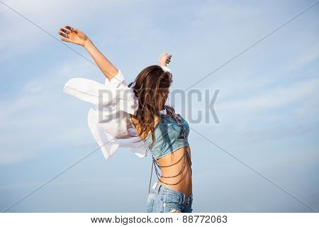 young carefree woman with hands up in blue jeans and white shirt in motion against blue sky