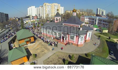 MOSCOW, RUSSIA - APRIL 19, 2014: Many people stand at long table near Sunday school in Church of Transfiguration Savior in Bogorodskoe during Holy Saturday before Easter, aerial view