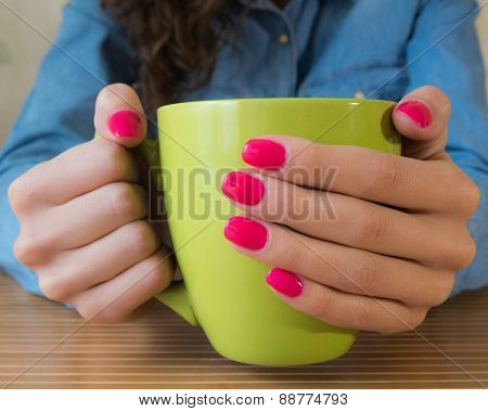Hands Of A Young Girl With Red Nail Polish Holding A Big Green Cup Of Tea