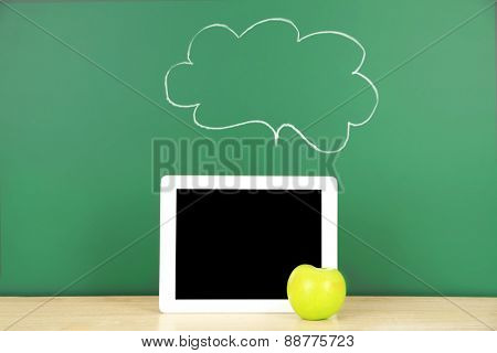 Tablet on table, on green blackboard background