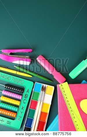 Bright school supplies on blackboard background