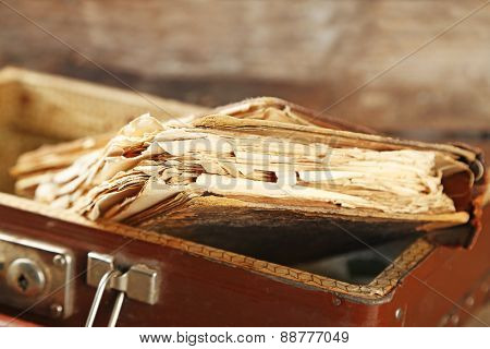 Old wooden suitcase with old books on wooden background