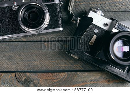Old retro cameras on rustic wooden planks background