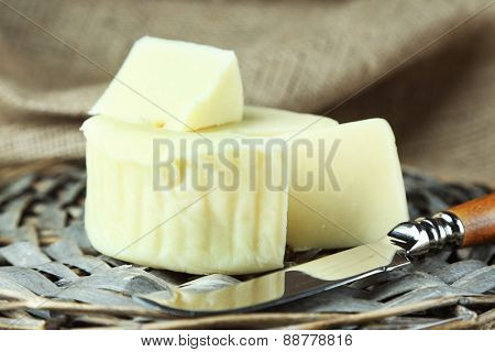 Cheese on wicker tray and sackcloth, closeup