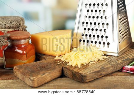 Grated cheese on wooden cutting board on blurred background