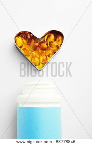 Heart of cod liver oil and jar with capsules, isolated on white