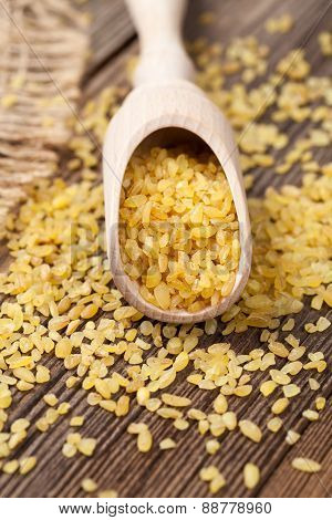 Natural healthy bulgur asian wheat grain in spoon on vintage bac