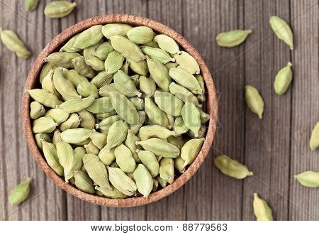 Green cardamom ayurveda plant spice in a wooden bowl on vintage