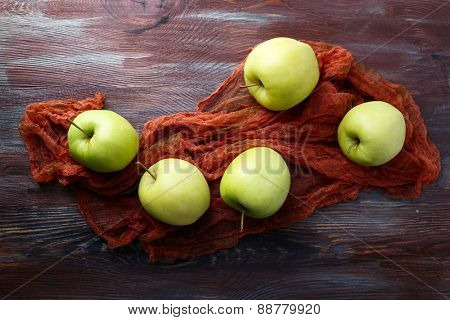 Green apples on wooden table with fabric, top view