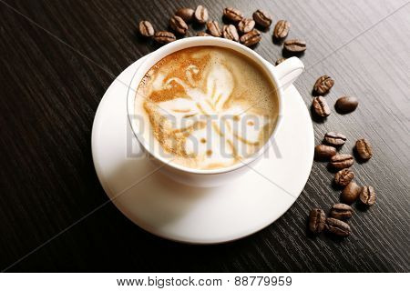 Cup of latte art coffee with grains on wooden background