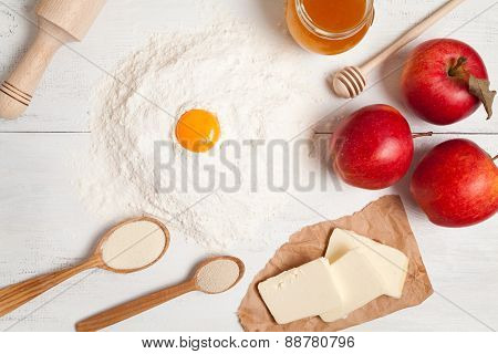 Preparation of pie Flour, butter, apples and yeast on white table