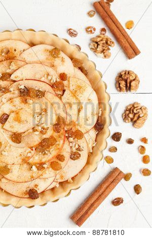 Homemade rustic apple pie preparation recipe. Tart with cinnamon, raisins and nuts on white table