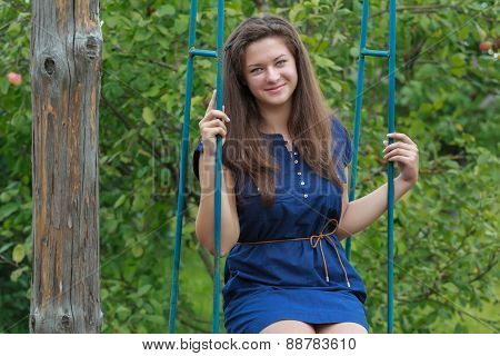 Portrait of brunette girl in navy blue sundress sitting on handmade swing